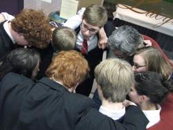 "Sitka debaters ""huddle"" to strategize."