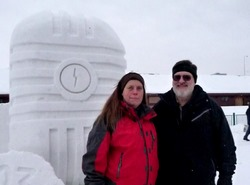 Suzi and Rich McClear pose in front of the KNBA snow sculpture (a giant microphone) at the Anchorage Fur Rondy.