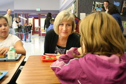 Alaska First Lady Sandy Parnell chats over a Fish -to-Schools lunch at Keet Gooshi Heen Elementary School in Sitka in April, 2012. (KCAW photo/Ed Ronco)