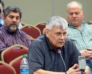 Kootznoowoo's Peter Naoroz, left, and seiner Bob Thorstenson, right, listen as Subsistence Regional Advisory Council Chairman Bert Adams presents recommendations to the Federal Subsistence Board earlier this year.