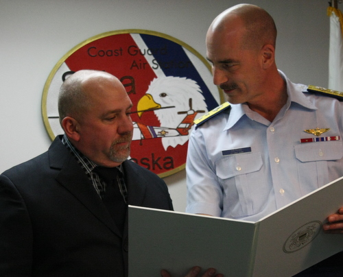 Howard Merkel, left, receives an award from Coast Guard Rear Adm. Thomas Ostebo. Merkel used his boat to assist in a rescue in early 2012. (KCAW photo by Ed Ronco)