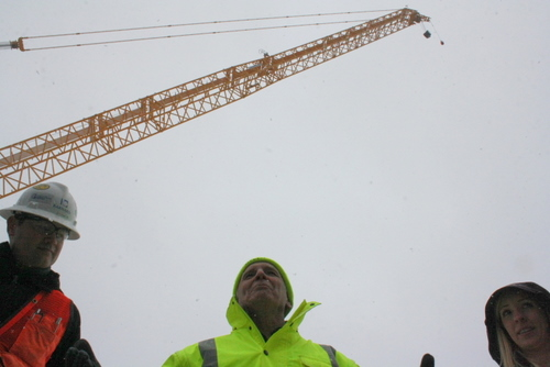 Clif Stump, of Barnard Construction, along with Richard Linden and Jessica Stockel of McMillen LLC, answer questions from the public beneath the massive crane at the Blue Lake dam expansion site. Some 74 members of the public took a tour of the construction site on Sunday afternoon (KCAW photo by Ed Ronco)