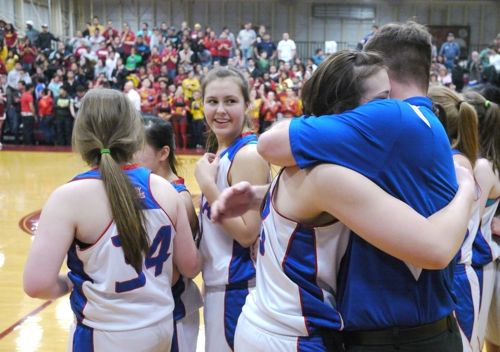 Sitka Lady Wolves coach Rich Krupa throws a bear hug around his team after winning the final of the 3A Region V tournament. (KCAW photo/Robert Woolsey)