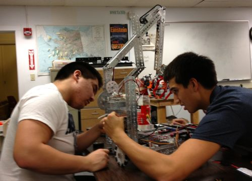 Mt. Edgecumbe students Gusty Akelkok (l) and Nick Bouker (r) prep their robot for the state meet. (MEHS photo/Mark Nance)