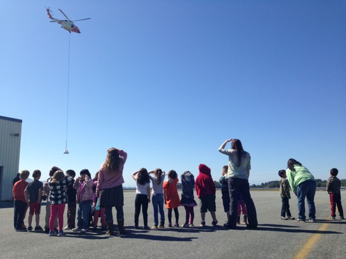 Jacquie Hedrick's Baranof Elementary kindergarten class watches an Air Station Sitka H-60 Jayhawk sling load fertilizer to Redoubt Lake for the U.S. Forest Service on Wednesday. The fertilizer is used to help sustain the red salmon fishery in Redoubt Lake. (USCG photo by Lt. David Birky)