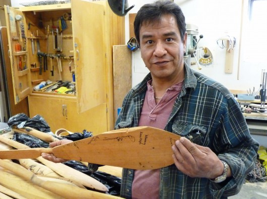 Carver Doug Chilton holds a lost canoe paddle that was chewed on by a bear before it could be recovered. Photo by Ed Schoenfeld, CoastAlaska News.