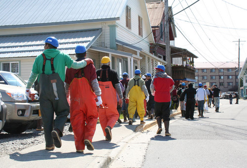 Workers from seafood processors near downtown Sitka walk down Katlian Street after being evacuated Monday morning. An ammonia leak from a tied-up vessel forced the closure of the road and the evacuation of nearby buildings. (KCAW photo by Erik Neumann)
