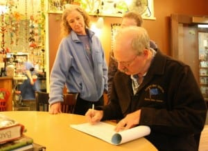 State Sen. Bert Stedman signs his name to a petition to repeal Senate Bill 21, as his wife, Lureen, and daughter Susan look on. If successful, the petition would put the question before voters in August 2014. Organizers must gather more than 30,000 signatures from across the state. (KCAW photo by Ed Ronco)