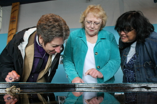 Episcopal Church Presiding Bishop Katharine Jefferts Schori, left, looks into a touch tank at the Sitka Sound Science Center with St. Peter's deacon Glenda Quintana, and interim rector Bishop Carol Gallagher. Jefferts Schori, a former oceanographer, has led the Episcopal Church since 2006. She's touring nine communities in Alaska. (KCAW photo by Ed Ronco)
