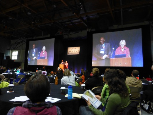 Lenwood Sloan, left on the screens, was keynote speaker at the Alaska Travel Industry Association conference. (Rich McClear/KCAW)