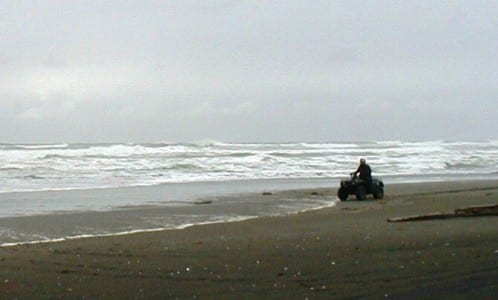 An ATV'er rides along a Yakutat beach where a wave-energy system is to be installed. A Boston-based company will try out the first device in 2015. (Ed Schoenfeld/CoastAlaska News)