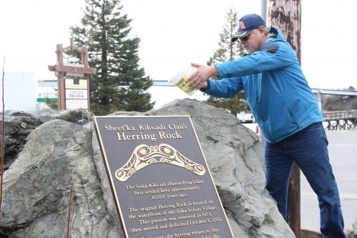 Andrew Roberts pours water on the Herring Rock, during a ceremony in Sitka Tuesday morning. (KCAW photo/Emily Forman)