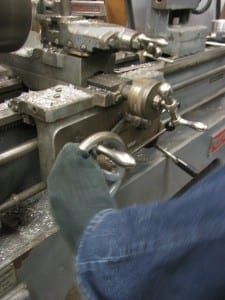 Having limited use of his hands, Partido operates the lathe with his toes. (KCAW photo/Robert Woolsey)