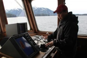 Captain Lito Skeek, of Petersburg, keeps an eye on the Kestrel's sonar during a survey of Sitka Sound. (KCAW photo/Rachel Waldholz)