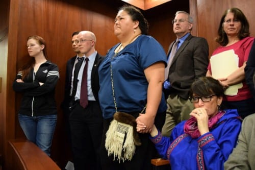In the Senate gallery, an emotional Rep. Charisse Millett holds hands with Liz Medicine Crow while Senators debate the fate of the bill. The legislation, which passed moments later, makes 20 Alaska Native languages official state languages alongside English. (Photo by Skip Gray/Gavel Alaska)