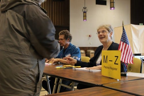 Poll worker Kathleen Brandt greets voters at primary day in Sitka's Harrigan Centennial Hall. (KCAW photo/Rachel Waldholz)