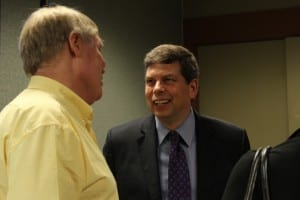 U.S. Senator Mark Begich speaks to Sitka resident Dirk White at the Sitka Chamber of Commerce. (KCAW photo/Rachel Waldholz)