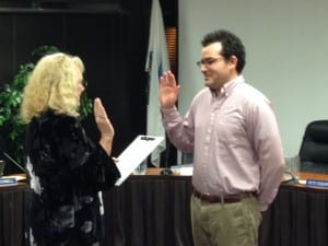 Colleen Ingman (l) administers the oath of office to new Assembly member Tristan Guevin. Another new assembly member, Steven Eisenbeisz, was out of town. (KCAW photo/Robert Woolsey)