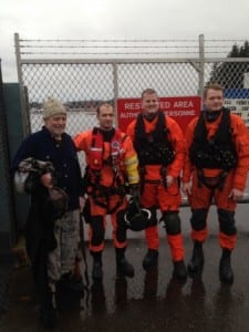 John Delong stands with Petty Officer 2nd Class Brendan Dent, Petty Officer 2nd Class Jason Vaughn and Petty Officer 3rd Class Ryan Ransom from Coast Guard Air Station Sitka after his rescue. (U.S. Coast Guard photo by Cmdr. Pete Melnick)