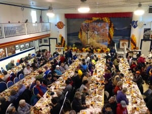 """Servers carried plates of turkey and mashed potatoes from the kitchen and called out, """"Who needs to be fed?"""" Hands shot up. (Emily Kwong/KCAW photo)"""