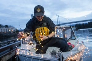 Paul Norwood strings lights aboard the Fucus. (Mike Hicks/KCAW photo)