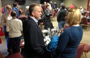 "Sen. Dan Sullivan chats with Chamber board member and Baranof Island Brewery Co. owner Suzan Hess. Sullivan told Sitka's business community that the key to paying down the national debt was ""growing the economy."" (KCAW photo/Robert Woolsey)"