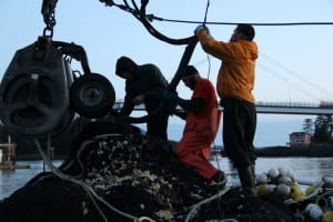 Crew members on the Star Shadow make repairs after the second day of herring fishing in 2015. From left: Brandon Ihde, Billy Nestle, and Devin Jones. (Rachel Waldholz/KCAW)