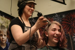 15-year-old Celia Lubin has her head shaved during the 2013 St. Baldrick's Fundraiser in Sitka. (KCAW photo/Rebecca LaGuire)
