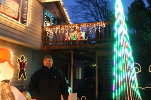 Mike Romine stands in front of his home on Wachusetts Street. He even provided a low-power FM signal so viewers could listen to holiday music in their vehicles. (KCAW photo/Brielle Schaeffer)