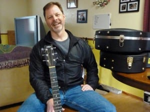 Juneau guitarist, singer and songwriter Kray Van Kirk talks about his music in his dining room. He'll perform during the Alaska Folk Festival, April 4-11 in Juneau. (Photo by Ed Schoenfeld/CoastAlaska News)