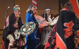 Wayne Carlick, left, and others drum as more than 30 people take the stage during Celebration 2016. The Atlin, British Columbia, group included relates from Juneau. (Photo by Ed Schoenfeld/CoastAlaska News)
