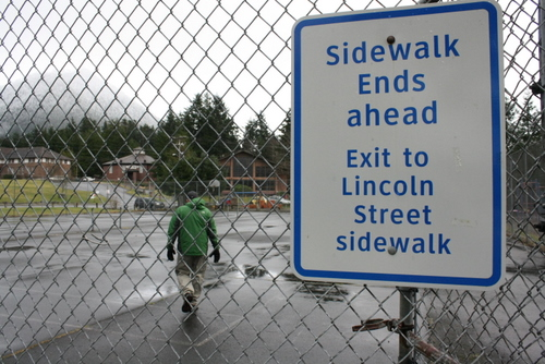 A sign instructs Jay Lageschulte, of Omaha, Neb., to cut across the tennis courts in Sitka, during a walk from Crescent Harbor to the Sitka National Historical Park on Feb. 13, 2013. A seaside walkway proposed for the shoreline between the two sites would simplify the route. (KCAW file photo by Ed Ronco)
