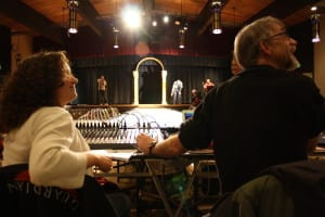 Chelsey Wheeler and Peter Apathy confer with an artist about music during dress rehearsal at Sitka's Wearable Arts Show. (Photo by Ed Ronco/KCAW)