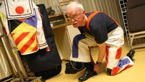 """Bill Foster, 74, puts on his wearable art before Wednesday night's dress rehearsal at the Sitka Wearable Arts Show. The title of Foster's outfit is """"In the Navy,"""" and is comprised of 13 maritime signal flags attached to a U.S. Navy sailor suit. (Photo by Ed Ronco/KCAW)"""
