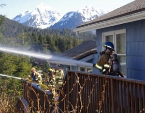 Firefighters used the decks of neighboring homes to attack the fire from different angles. It took more than two hours to extinguish. (Photo by Roberta White/Sitka Fire Department)