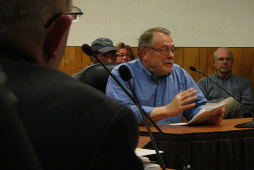 Sitka Historical Society President John Stein testifies to the Assembly as Interim City Administrator Jay Sweeney looks on in the foreground. Stein is hoping the Assembly will restore a $20,000 cut in the city's contribution to his group. (KCAW photo by Ed Ronco)