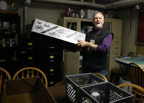 Charlie Bean uses fish boxes to pack up his workspace at the Bill Brady Healing Center. He jokes that people in other states probably don't use fish boxes like this. (KCAW photo by Ed Ronco)