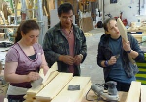 Doug Chilton works with students in a paddle-carving class.