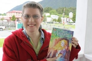 """Sitka resident Marjean Ragsdale poses with her book, """"Anstice."""" The cover was designed by Sitka artist Jessica Lynn Clark. (KCAW photo by Ed Ronco)"""