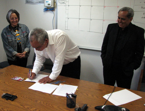 Sealaska vice-chair Rosita Worl and chair Albert Kookesh look on as STA Council chair Michael Baines signs a management agreement for Redoubt Falls.