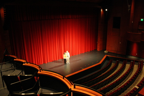 Sergio Fisher and his wife, Fay, stand on the stage at the Performing Arts Center in Sitka. Fisher was the architect who designed the interior of the theater. It was his first time back to Sitka since the building opened in 2007. (KCAW photo by Ed Ronco)