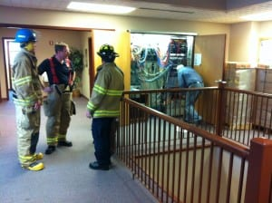 Firefighters discuss how to handle a leaky battery in Sitka's city hall on Monday morning. (KCAW photo by Ed Ronco)