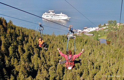 Zipline riders watch a cruise ship anchored near Hoonah's Icy Strait Point tourist attraction as they descend. The state is blocking a grant to build a new cruise-ship dock because the attraction and cruise lines object to its location. Photo Courtesy Icy Strait Point.