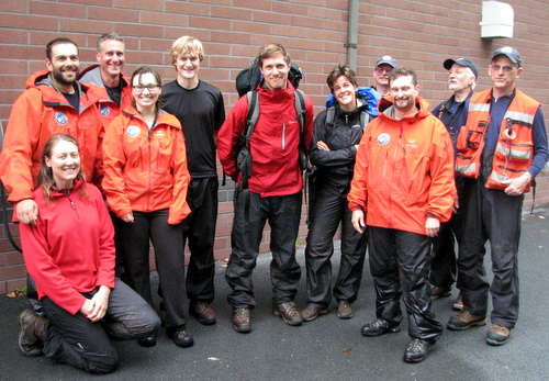 KCAW news intern Erik Neumann and his friend, Lacey Carnahan, pose at the firehall with the Sitka Mountain Rescue team  who assisted them off Lucky Chance ridge. (KCAW photo/Robert Woolsey)