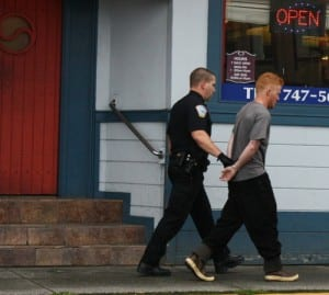 Tyler Westlund, 22, is taken into custody by Sitka police. Westlund is accused of running from the Pioneer Bar with a gun that had just been fired inside the bathroom. He's charged with tampering with physical evidence.