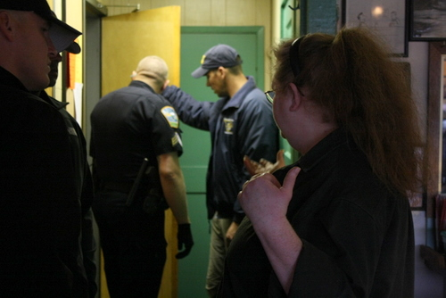 A bartender talks with Alaska State Troopers outside the bathrooms inside the Pioneer Bar after an apparent argument ended in gunfire inside the men's room. Further details were not immediately available. (KCAW photo by Ed Ronco)