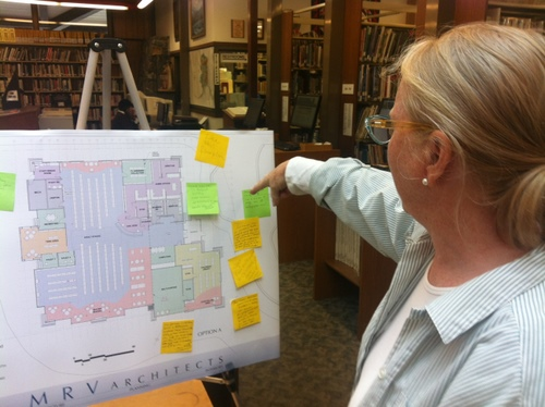Kettleson Memorial Library Director Sarah Bell reads from sticky notes attached to architect plans for the library's expansion. (KCAW photo by Ed Ronco)