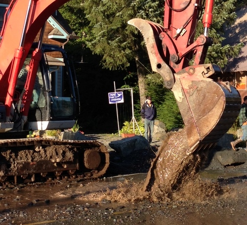 A man watches as heavy equipment works on a water main break in the 700 block of Sawmill Creek Road in October. Repeated repairs like this have