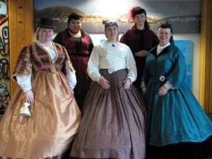 Alaska Day greeters in 1860s style attire at the Sitka airport. (KCAW photo by Emily Forman)
