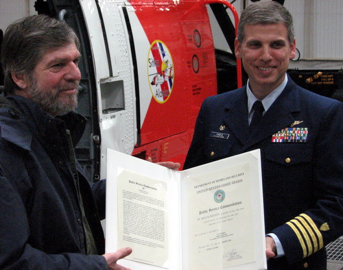 John Hagen (l.) receives his commendation from Air Station SItka commander Cpt. Ward Sandlin. (KCAW photo/Robert Woolsey)